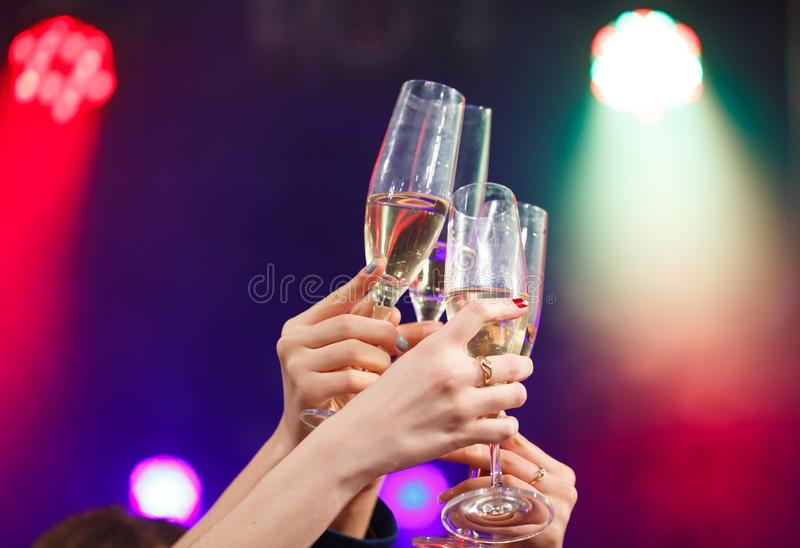 Clinking glasses of champagne in hands on bright lights background. stock image
