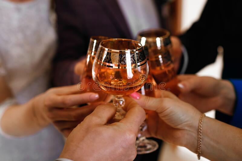 Clinking of glasses at a party, whiskey, cognac and champagne, fun of a big company royalty free stock images