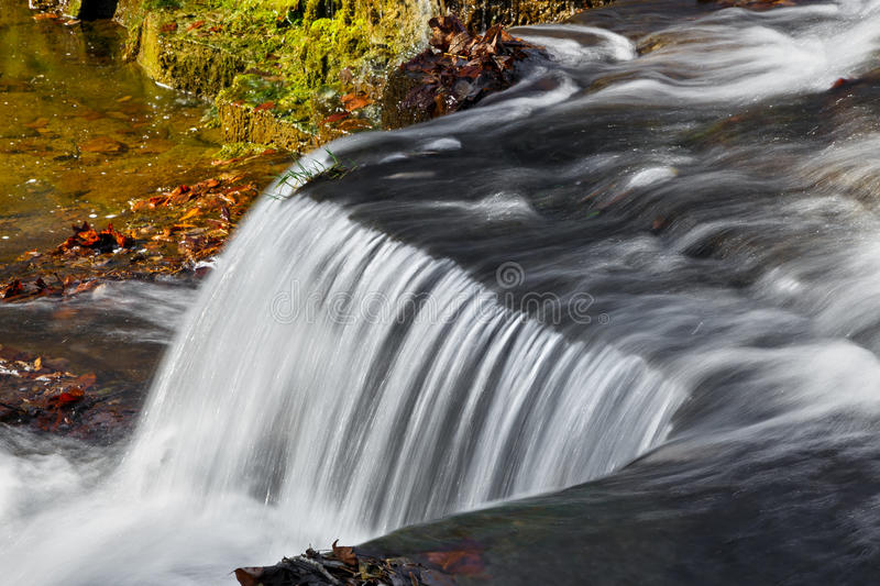Clinton Falls Flow. Water flows over a jagged rock ledge of Clinton Falls, a waterfall in rural Putnam County, Indiana royalty free stock photo
