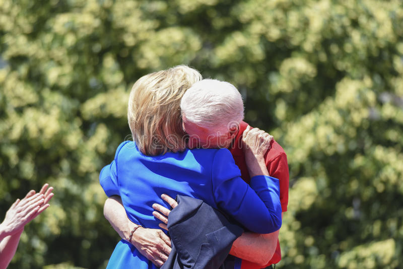 Clintons embrace. Bill and Hillary Clinton embrace in direct sunlight with foliage in the background after she announced her candidacy for the 2016 Democratic stock photo