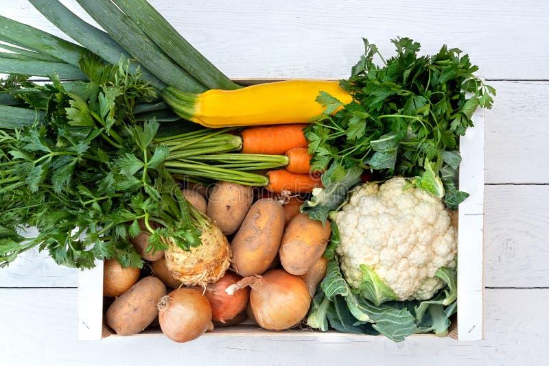 Clioseup drewniany pudełko świezi warzywa od rolników wprowadzać na rynek na biel malującym drewno stole z góry obrazy royalty free