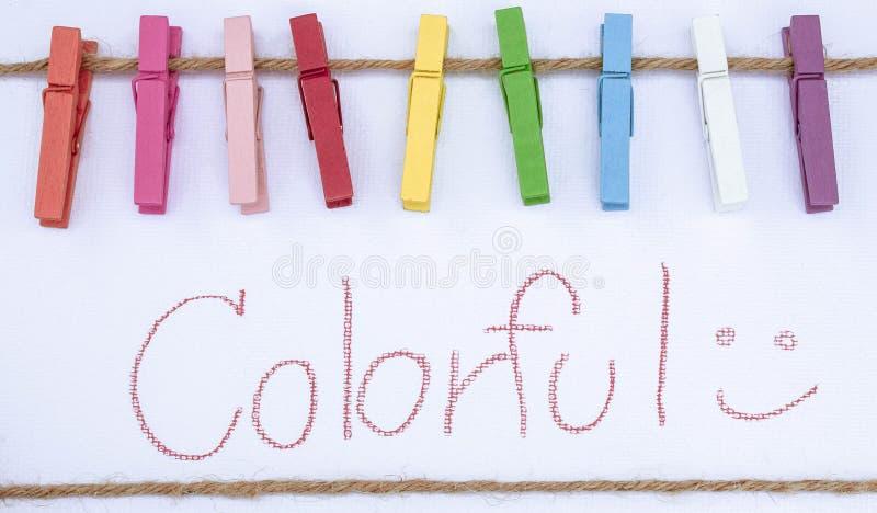 Clip de madera del color en colorido de la escritura de la cuerda y de la mano aislado en el fondo blanco Esto tiene trayectoria  imagenes de archivo