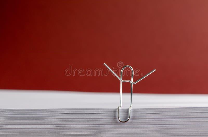 Clip de papel con las manos en alto en el Libro Blanco en fondo rojo imagenes de archivo