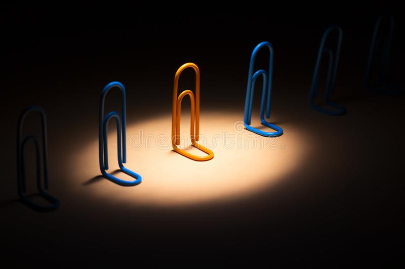 Clip highlighted by the spotlight from above among others,person chooses his or her way of life and the mood of an optimist, a. Clip highlighted by the spotlight royalty free stock photo