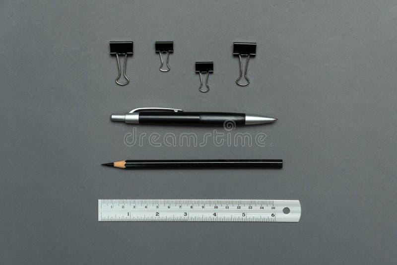 Clip negro de papel del lápiz de la pluma y material de oficina de plata de la regla en el papel gris para el fondo de la educaci foto de archivo libre de regalías