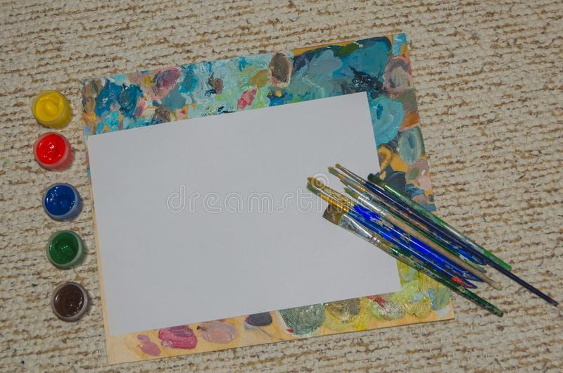 Clipart, white sheet of paper with brushes background stock images
