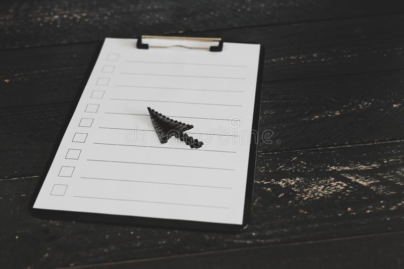 Clipboard with blank list with cases to tick off on wooden desk with mouse pointer style icon. Made of paper on top of it, concept of time management and stock images