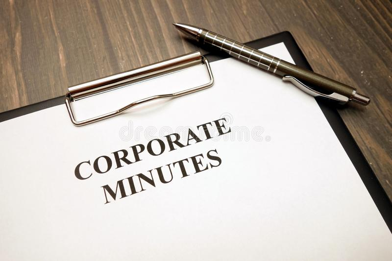 Clipboard with corporate minutes and pen on desk stock photography