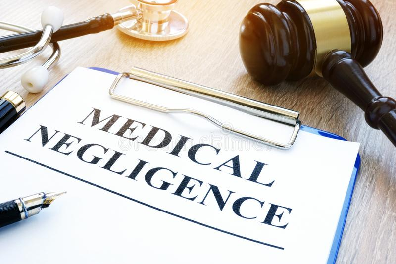 Documents about medical negligence on a table. Clipboard with documents about medical negligence on a table royalty free stock images