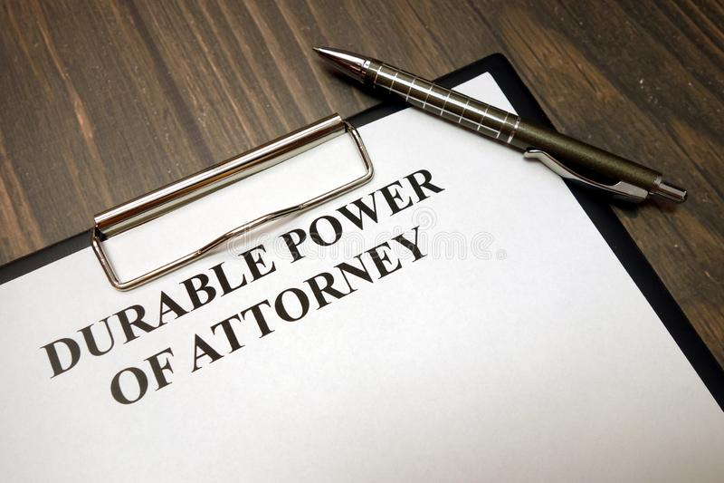 Clipboard with durable power of attorney and pen on desk. Clipboard with durable power of attorney and pen on wooden desk background stock image