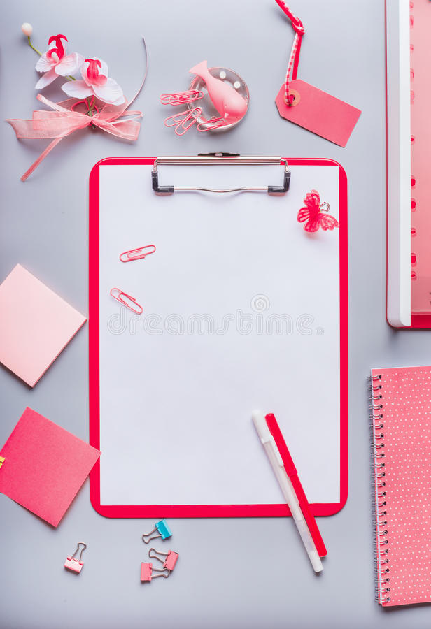 Clipboard with empty copy space blank for list or for input the text, flowers and other supplies, Top view, flat lay. Modern femi. Nine office desk table in pink royalty free stock images