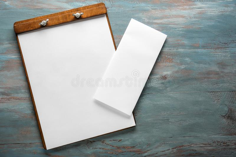 Clipboard with empty sheets of paper on wooden table stock images