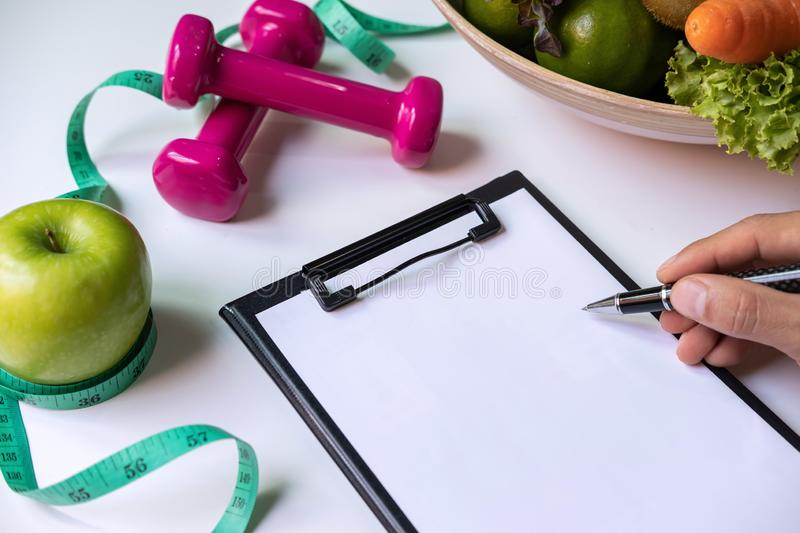 Clipboard with healthy fruit, vegetable and measuring tape on nutritionist desk diet concept royalty free stock images