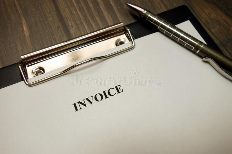 Clipboard with invoice and pen on desk stock photos