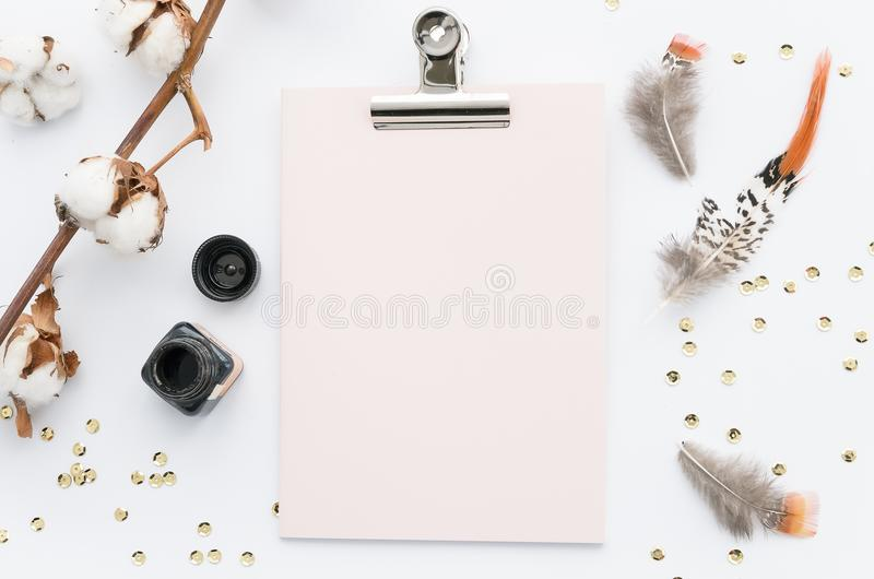 Clipboard mock up and colored feathers on white background. stock image