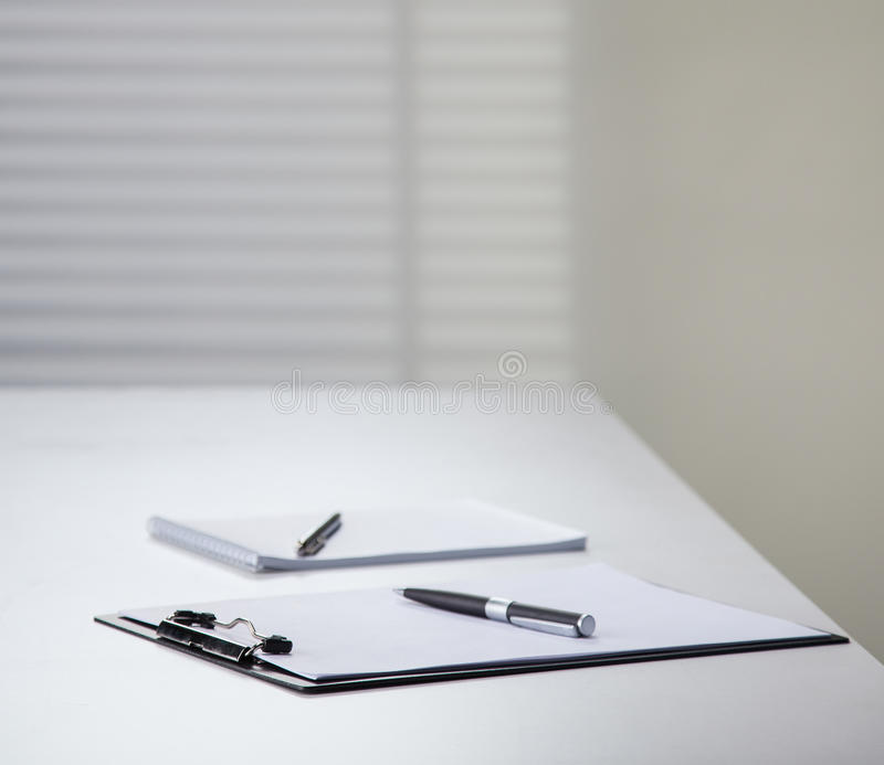 Clipboard and notebook with pens on a table. In the office royalty free stock images