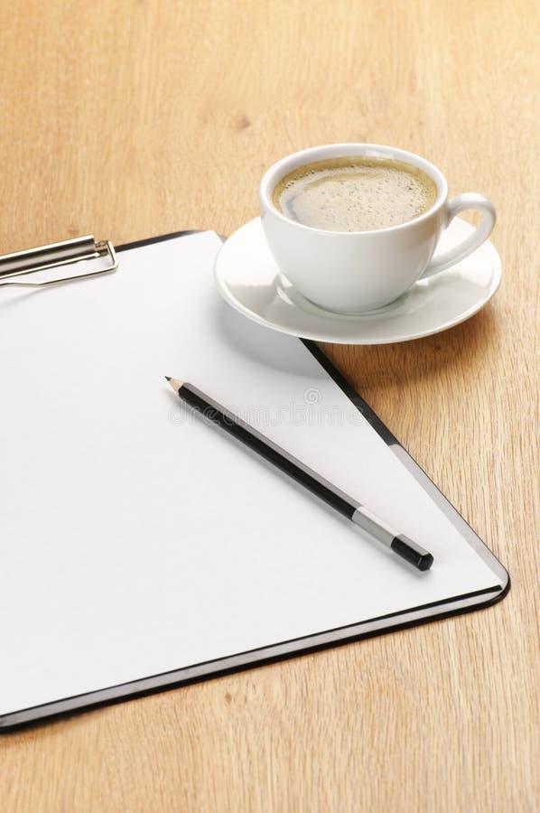 Clipboard och kaffe arkivfoto