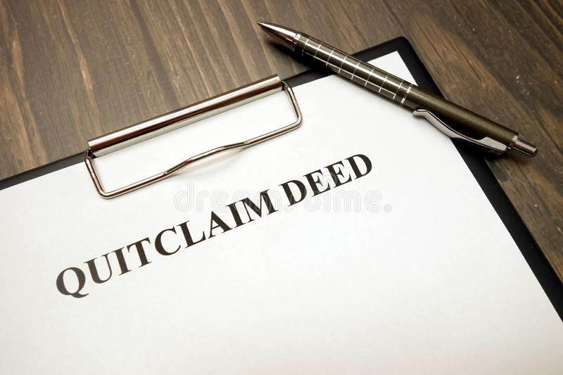 Clipboard with quitclaim deed on desk. Clipboard with quitclaim deed on wooden desk background royalty free stock photos