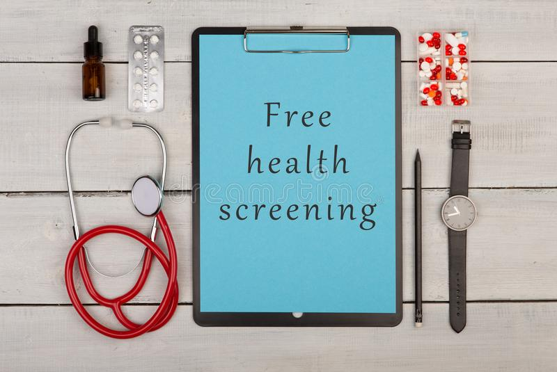 Clipboard with text & x22;Free health screening& x22;, pills, watch and stethoscope. Medecine concept - clipboard with text & x22;Free health screening& x22 royalty free stock photography