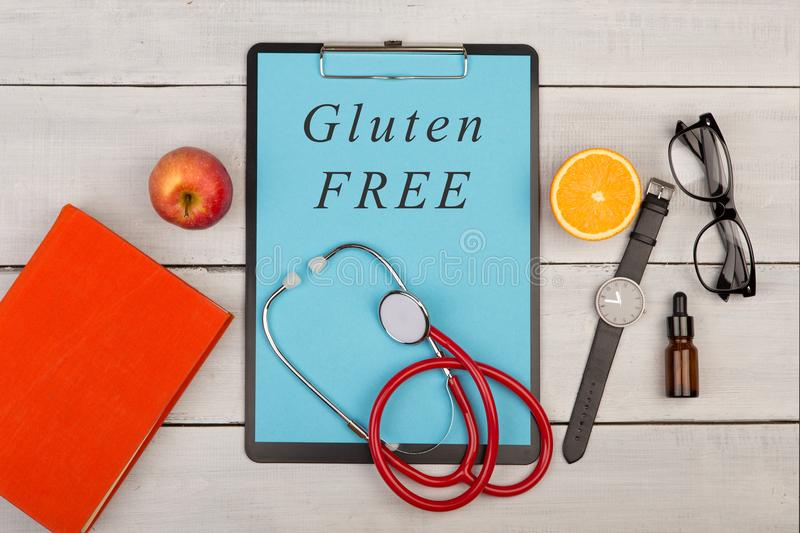 clipboard with text & x22;Gluten free& x22;, book, eyeglasses, watch, fruit and stethoscope royalty free stock image