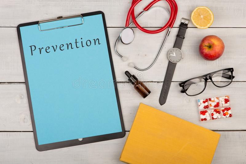 clipboard with text & x22;Prevention& x22;, pills, stethoscope, book, eyeglasses and watch royalty free stock image