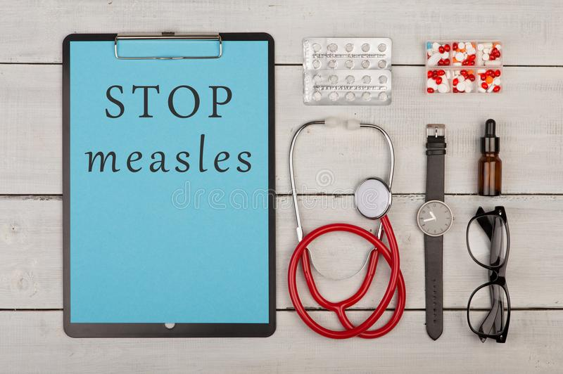 clipboard with text & x22;Stop measles& x22;, pills, stethoscope, eyeglasses and watch stock image
