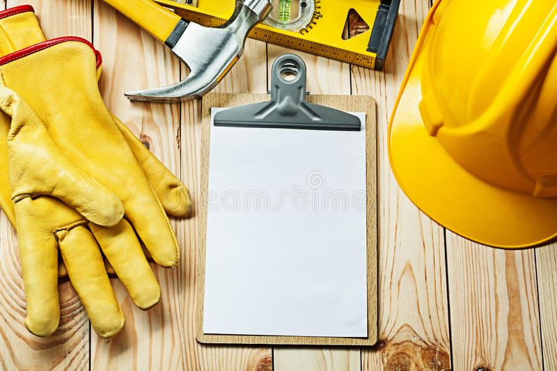 Clipboard with white blank paper sheet  for your text gloves hammer level helmet. Clipboard with white blank paper sheet for your text gloves hammer level helmet stock photos
