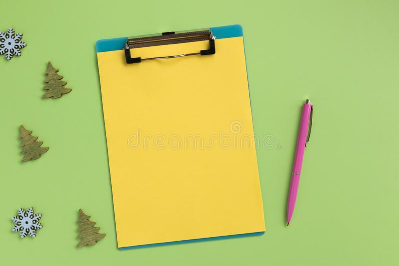 Clipboard with yellow sheet and christmas decor, on green background royalty free stock photos