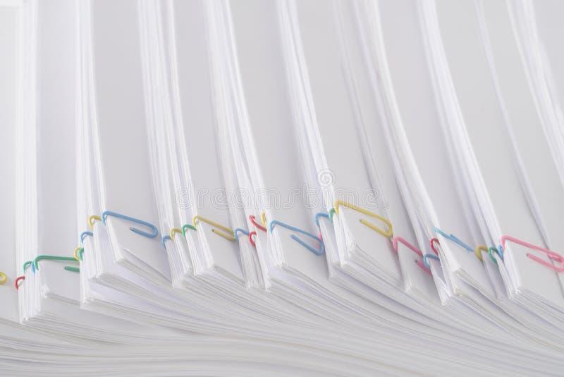 Clipe colorido com a pilha do documento e dos relatórios brancos da sobrecarga imagem de stock royalty free