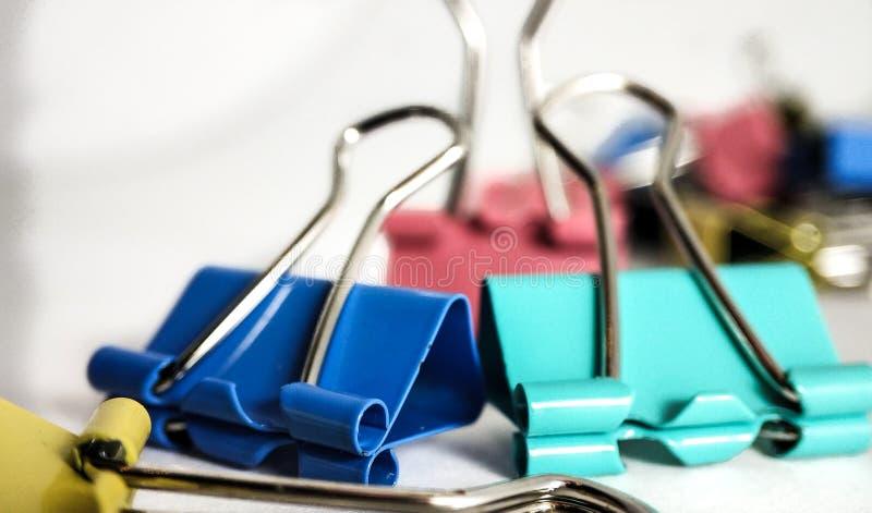 Clipes de papel coloridos em um fim da pilha acima em um fundo branco imagens de stock