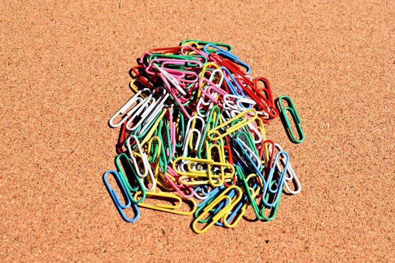 Clipes de papel coloridos isolados no fundo da cortiça fotografia de stock royalty free