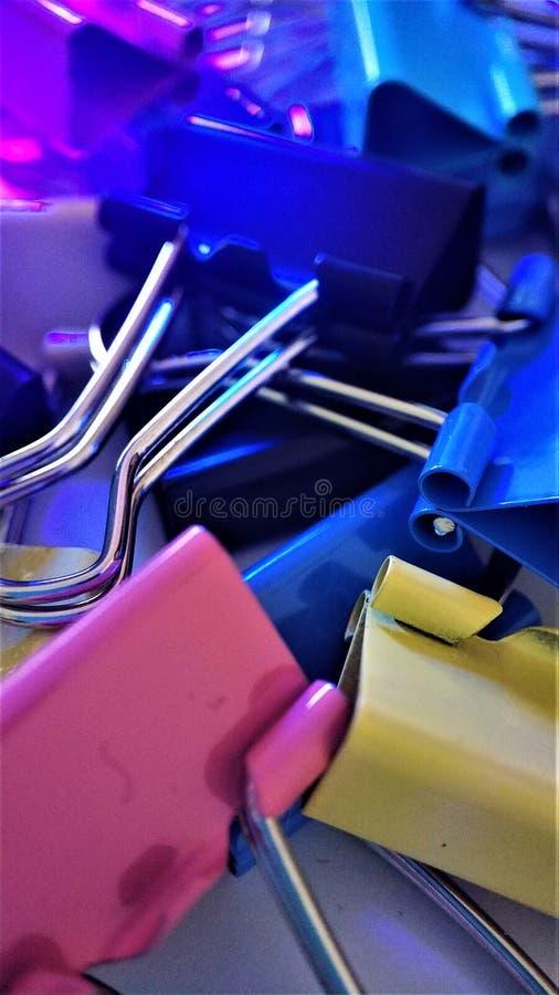 Clipes de papel coloridos sob raios do close up macro ultravioleta para o fundo fotografia de stock