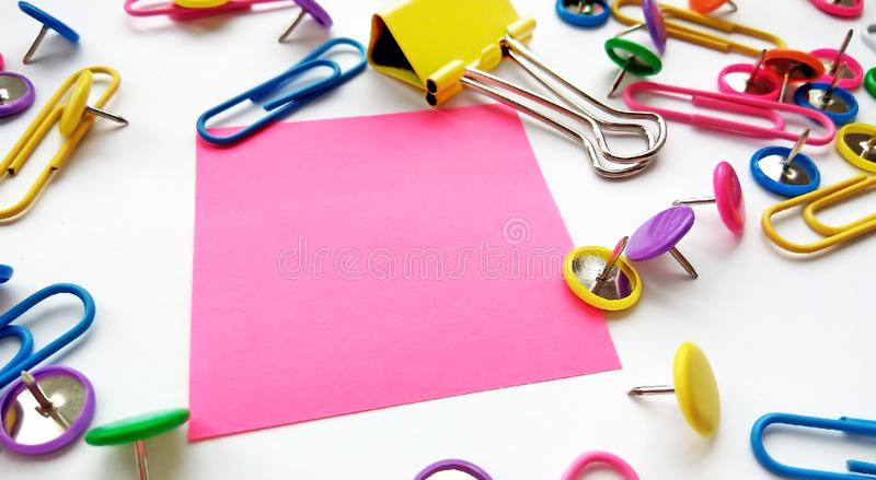 Clipes de papel da escola e dos materiais de escritório, pinos, notas amarelas, etiquetas no fundo branco foto de stock royalty free