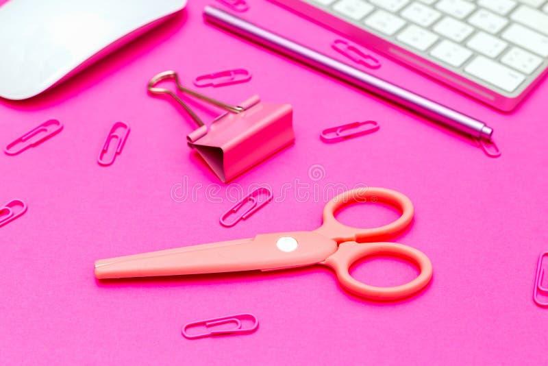 Clipes de papel Desktop e cor-de-rosa, tesouras no fundo cor-de-rosa pl?stico foto de stock