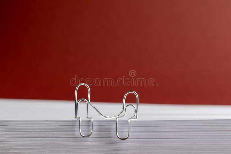 Clipes de papel que guardam as mãos na pilha de papel no fundo vermelho imagens de stock royalty free