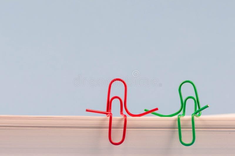 Clipes de papel vermelhos e assento verde em uma resma do Livro Branco e fala ou ter de uma conversação Uma foto com um espaço da foto de stock