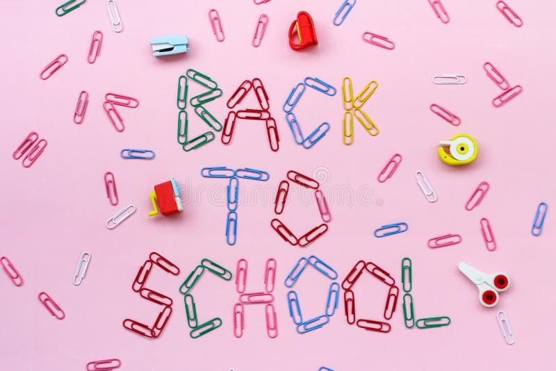 Clips de papel coloreados en un fondo rosado alineado con la inscripción - de nuevo a escuela fotografía de archivo libre de regalías