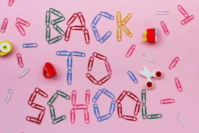 Clips de papel coloreados en un fondo rosado alineado con la inscripción - de nuevo a escuela fotos de archivo libres de regalías