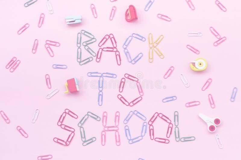 Clips de papel coloreados en un fondo rosado alineado con la inscripción - de nuevo a escuela foto de archivo libre de regalías
