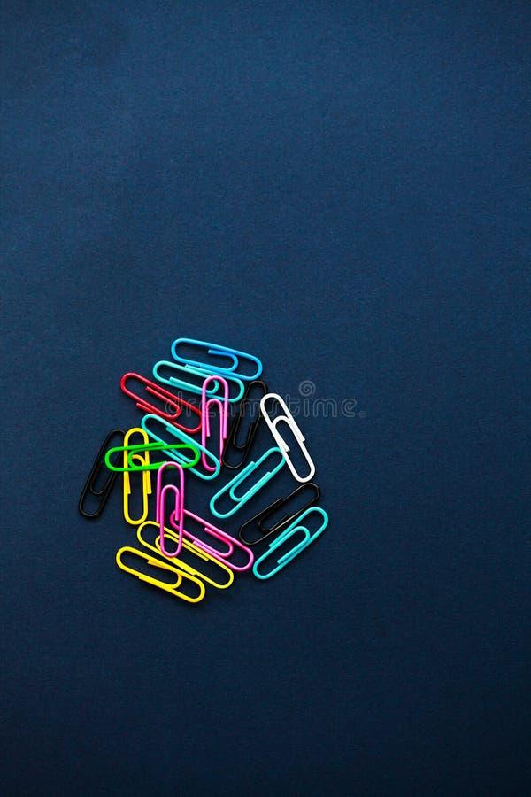 Clips de papel coloreados multi en fondo llano imagen de archivo