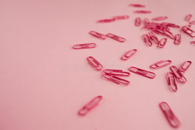 Clips de papel rosados dispersados Fondo rosado flatlay imagen de archivo