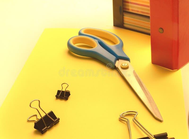 Clips de papel, tijeras y documento sobre la tabla contra la perspectiva de una carpeta y etiquetas engomadas para las notas foto de archivo
