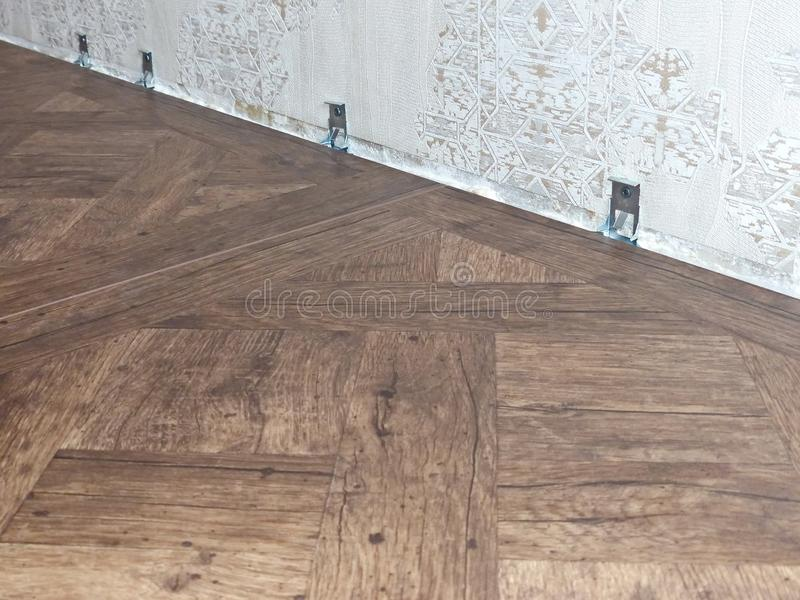 Clips system for laminate. Standard skirtings. Laying laminate flooring, repair the apartment with their own hands. Clips system for laminate. Laying laminate royalty free stock photography