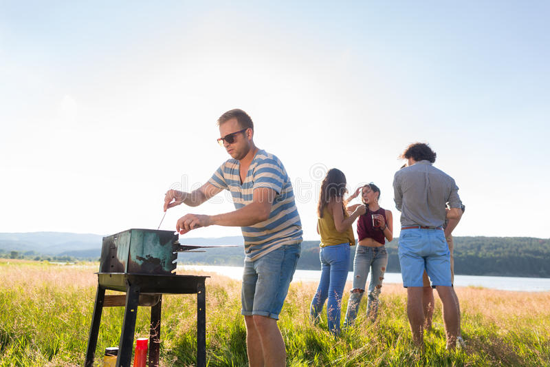 Clique des jeunes faisant le BBQ au lac images libres de droits