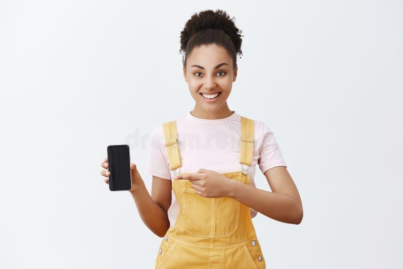 Clique este botão Estudante fêmea africano devista despreocupado nos brins na moda amarelos, guardando o smartphone e fotografia de stock