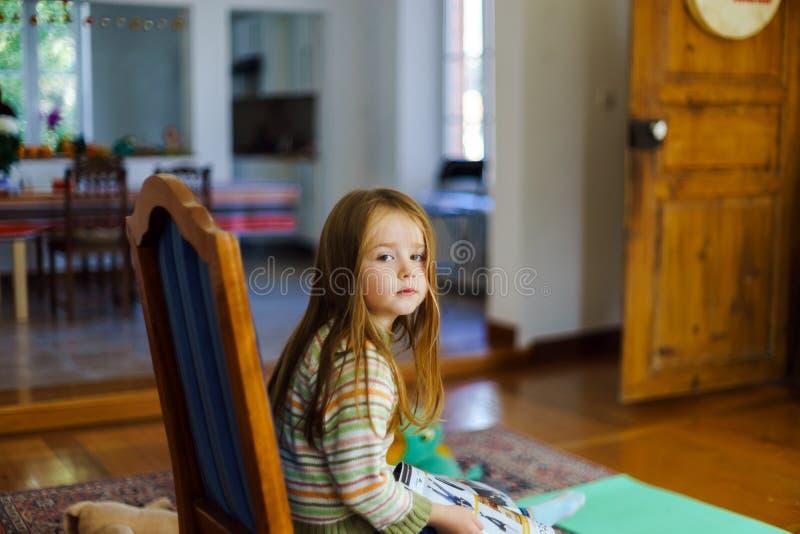 CLittle女孩坐椅子在客厅 库存图片