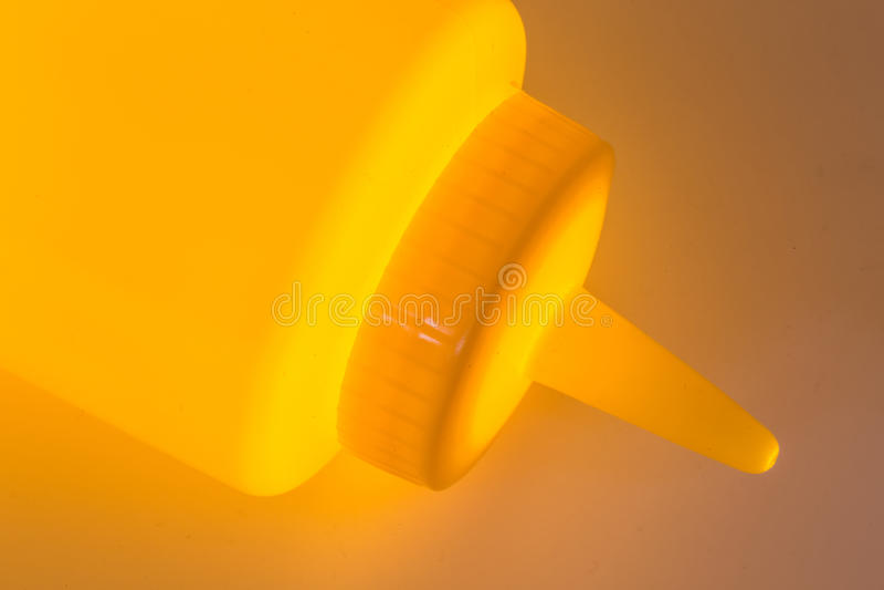 Clloseup en plastique jaune de bouteille de moutarde avec une lumière rougeoyante photographie stock libre de droits