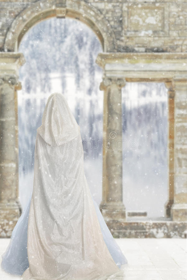 Cloaked woman by castle lake stock photos