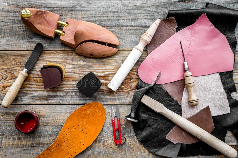 Clobber`s desk. Tools, wooden last, pieces of leather on wooden background top view.  stock photo