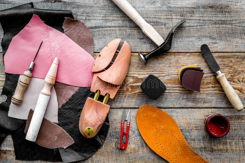Clobber`s desk. Tools, wooden last, pieces of leather on wooden background top view.  stock image
